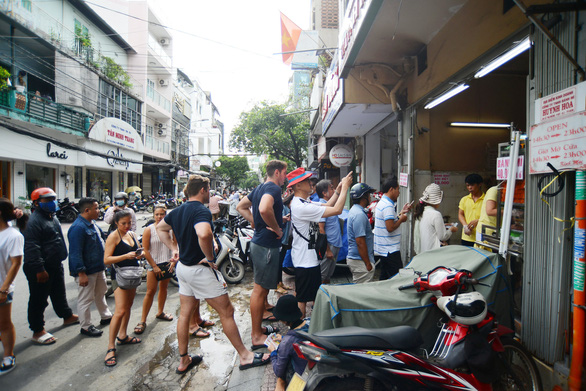 A file photo shows people including both locals and tourists queuing up to buy banh mi at a famous stall on Le Thi Rieng Street in Ho Chi Minh City's District 1. Photo: Quang Dinh / Tuoi Tre