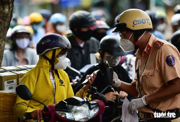 A police officer in Ho Chi Minh City guides a motorbike rider on how to complete health declaration, August 14, 2021. Photo: M.H. / Tuoi Tre