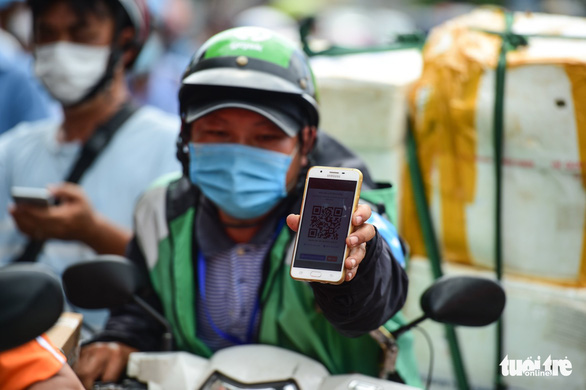 An app-based delivery worker presents a QR code he got after completing health declaration in Ho Chi Minh City, August 14, 2021. Photo: M.H. / Tuoi Tre