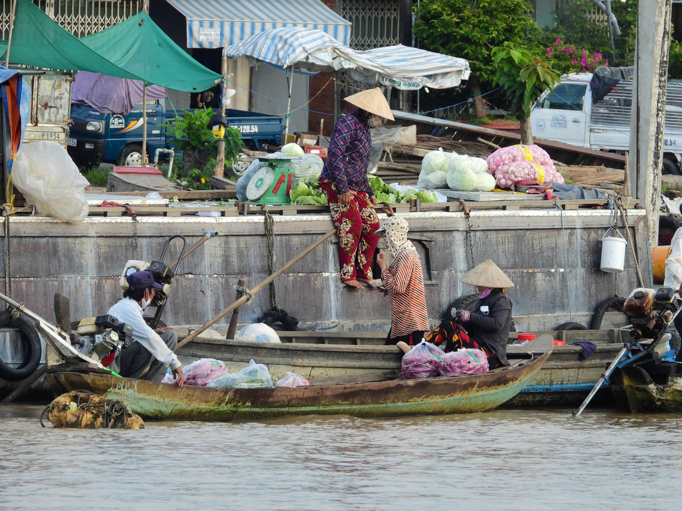 A sale is made at the Cai Rang Floating Market in Can Tho City, Vietnam, August 9, 2021. Photo: Tien Trinh / Tuoi Tre