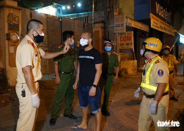 Ho Chi Minh City police confront a foreigner for flouting COVID-19 movement curb, August 17, 2021. Photo: Dan Thuan / Tuoi Tre