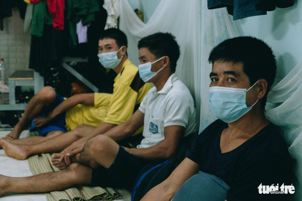 A group of construction workers shares a dorm room in Duong Noi Ward of Hanoi's Ha Dong District during a social distancing period that started in the city on June 2021.