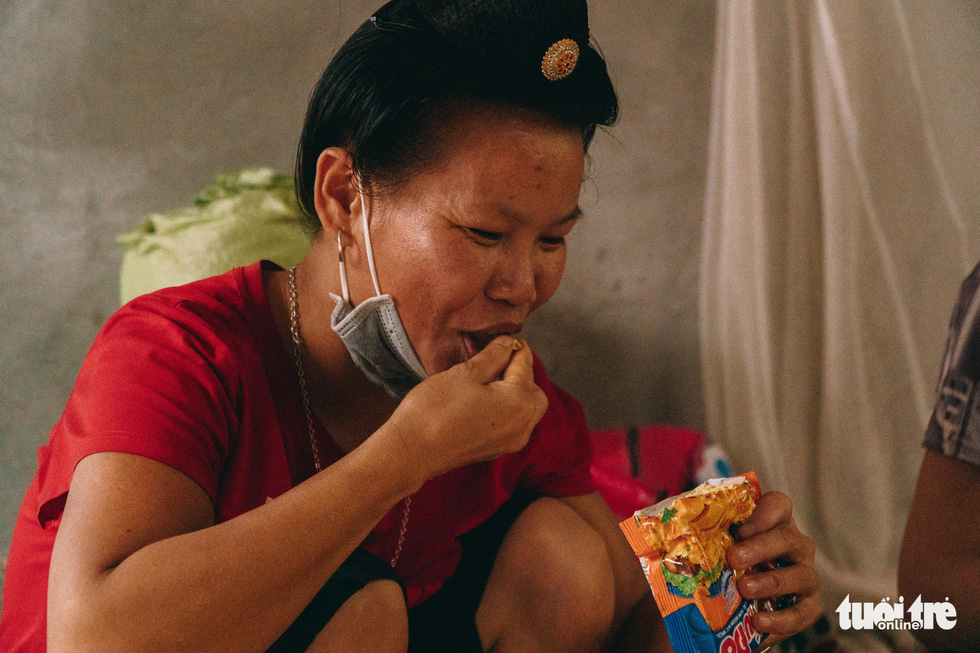 Lo Thi Bong, a migrant worker, eats an uncooked instant ramen pack.