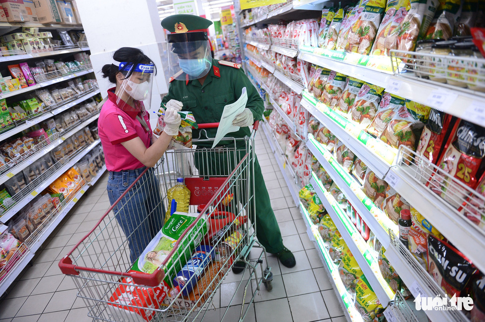 Soldiers pick up items for residents with the help of a Big C Mien Dong Supermarket staffer in District 10, Ho Chi Minh City, Vietnam, August 24, 2021.