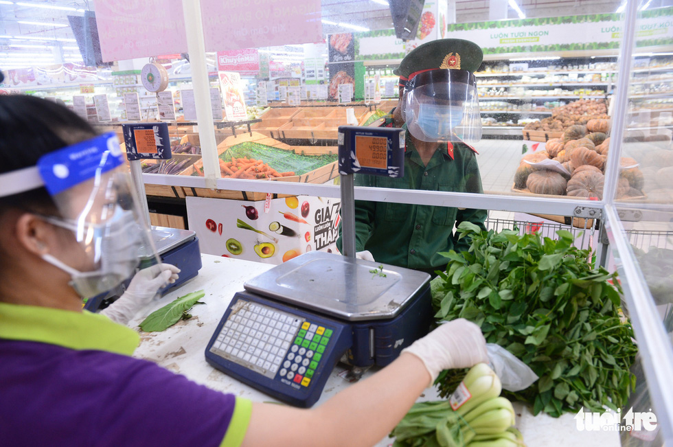 Soldiers pay for items at a checkout counter at Big C Mien Dong Supermarket in District 10, Ho Chi Minh City, Vietnam, August 24, 2021.