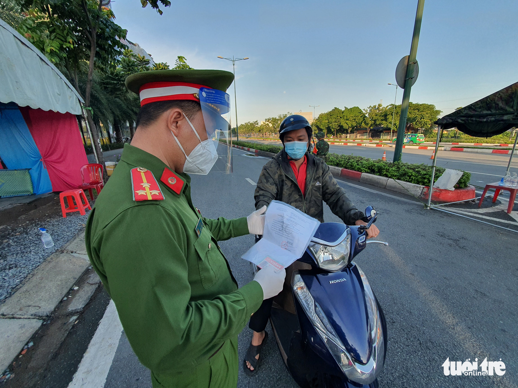 An officer examines documents of a resident in Binh Thanh District, Ho Chi Minh City, August 24, 2021. Photo: Minh Hoa / Tuoi Tre