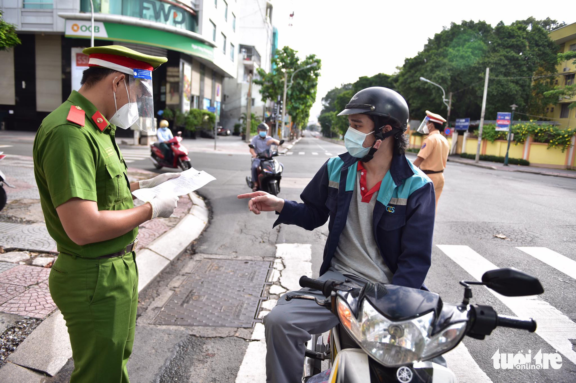 An officer examines documents of a resident in District 1, Ho Chi Minh City, August 24, 2021. Photo: Ngoc Phuong / Tuoi Tre