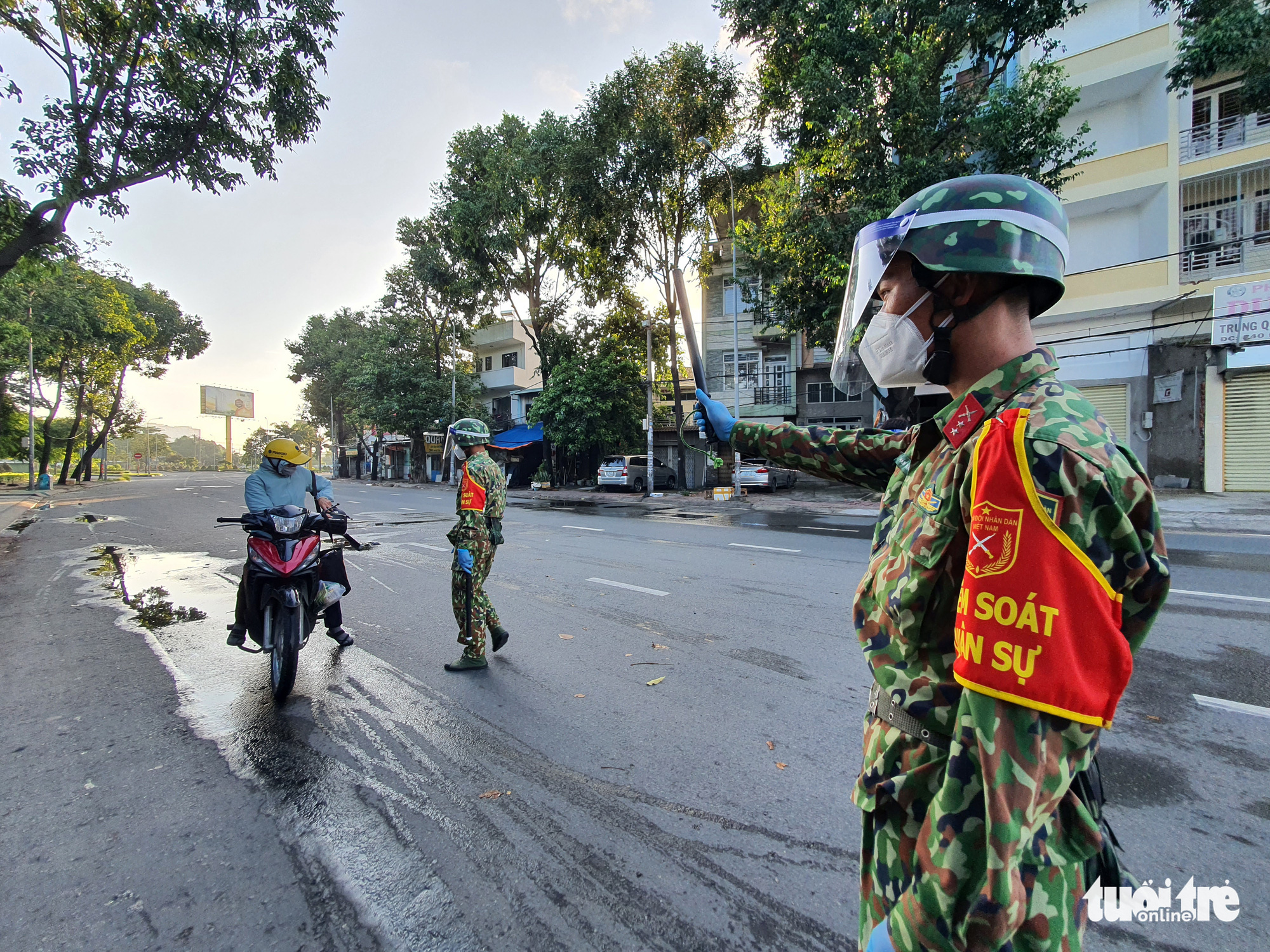 Military officers inspect a commuter on Dinh Bo Linh Street in Binh Thanh District, Ho Chi Minh City, August 24, 2021. Photo: Minh Hoa / Tuoi Tre