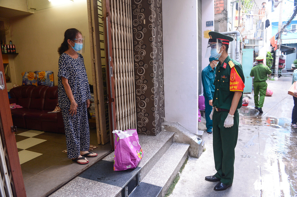 Soldiers deliver essential items ordered by a household in District 10, Ho Chi Minh City, Vietnam, August 24, 2021.