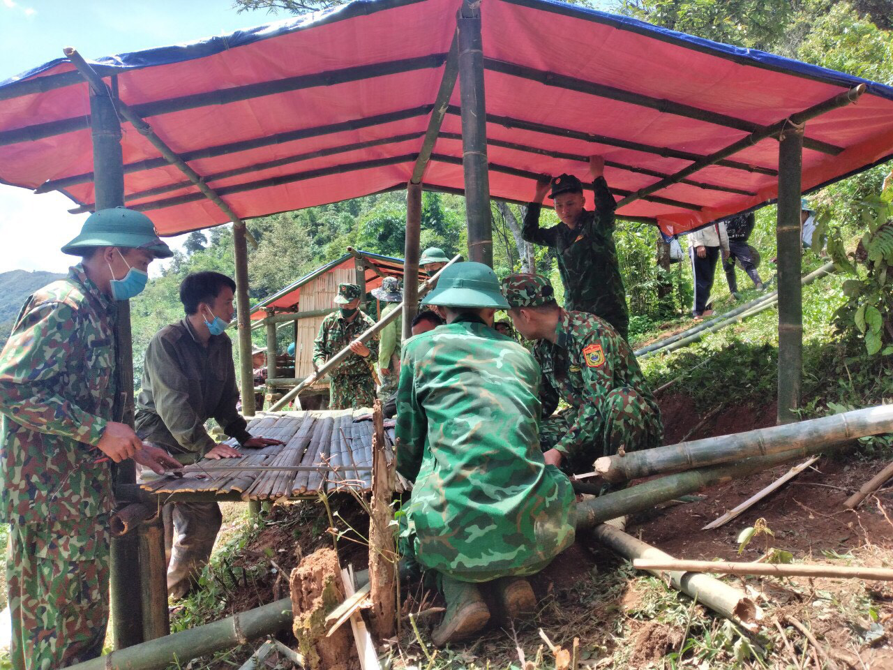 Officers build bamboo lodges on a mountain side in Mai Son District, Son La Province, Vietnam. Photo: Lo Thi Phien / Tuoi Tre