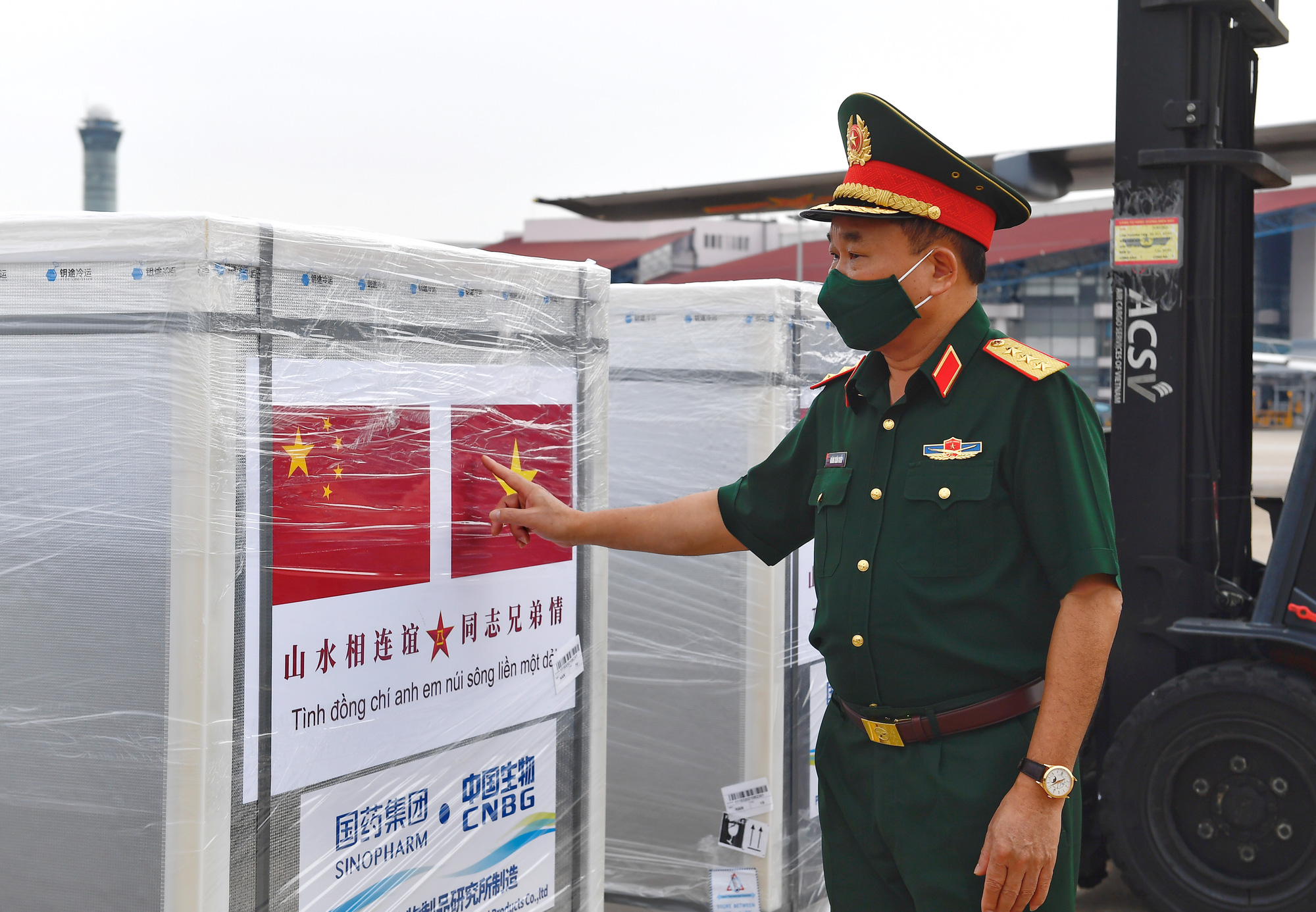 Vietnamese Deputy Minister of National Defense Hoang Xuan Chien stands next to the shipment of Sinopharm vaccine at Noi Bai International Airport in Hanoi, August 23, 2021 in this supplied photo.