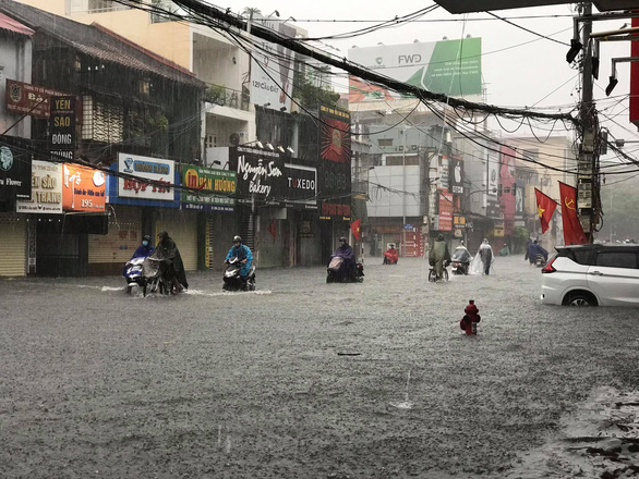 Hai Phong City residents travel along an inundated street, August 26, 2021. Photo: Tien Thang / Tuoi Tre