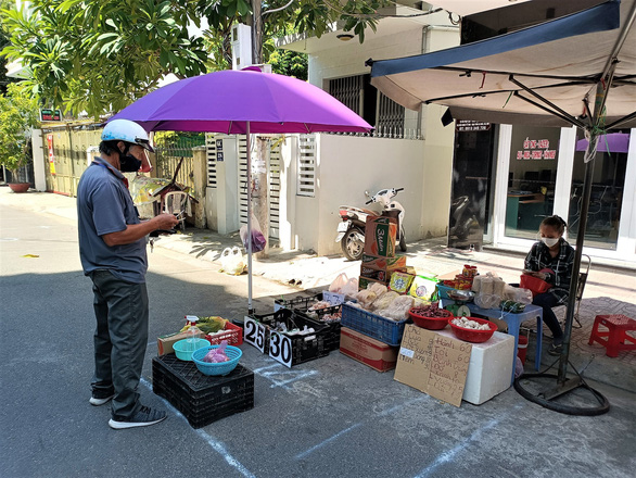 A member of a response team in Nha Trang City picks up grocery order for local residents at a coronavirus-safe food stall. Photo: Minh Chien / Tuoi Tre
