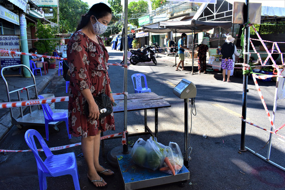 A market-goer weighs her item befeore paying a seller in a makeshift market in Nha Trang City. Photo: Minh Chien / Tuoi Tre