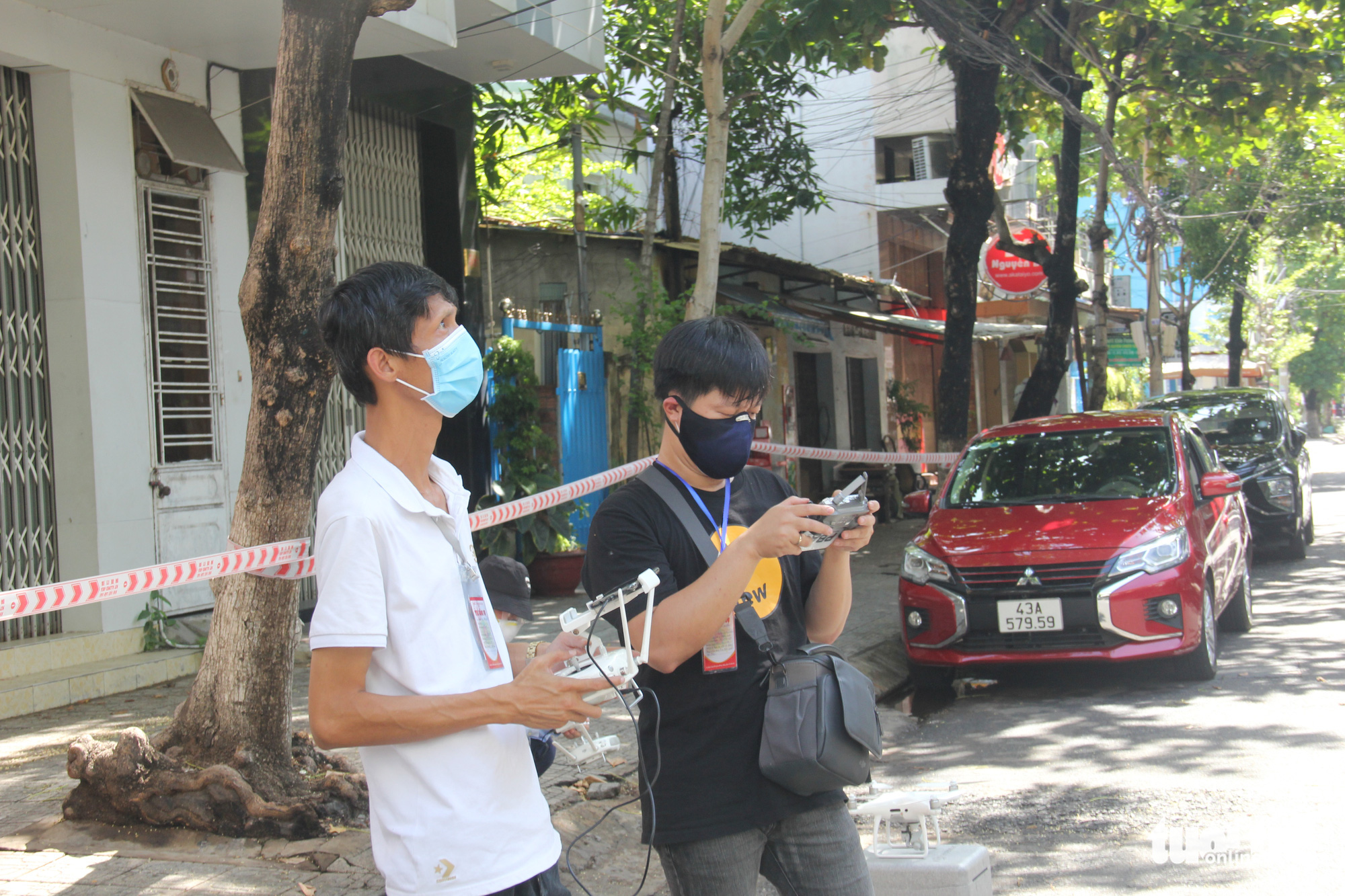 Two men operate camera drones to monitor the situation in an alley in Hai Chau District, Da Nang, August 29, 2021. Photo: Tuoi Tre