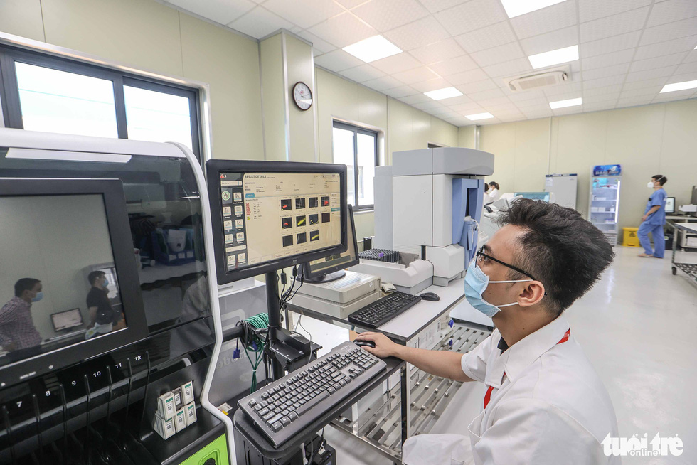 A technician operates a hematology analyzer at a newly-built COVID-19 field hospital in Hoang Mai District, Hanoi, August 31, 2021. Photo: Nguyen Khanh / Tuoi Tre
