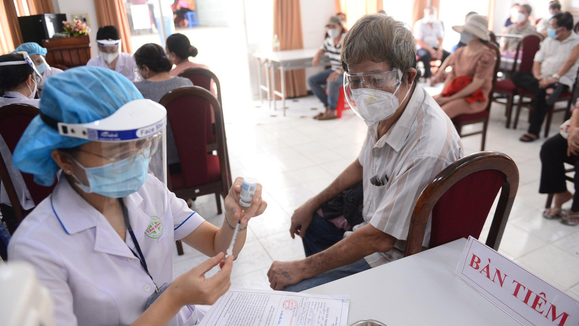 A medical worker prepares to administer a Moderna vaccine shot to a man above 65 years old in Tan Binh District, Ho Chi Minh City. Photo: Q. Dinh / Tuoi Tre