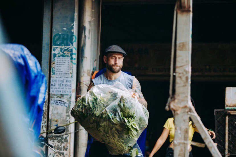 Matthew Donald is seen carrying vegetables donated by sellers at Ho Chi Minh City's Thu Duc Agricultural Product Market to local shelters. Photo by courtesy of Donald