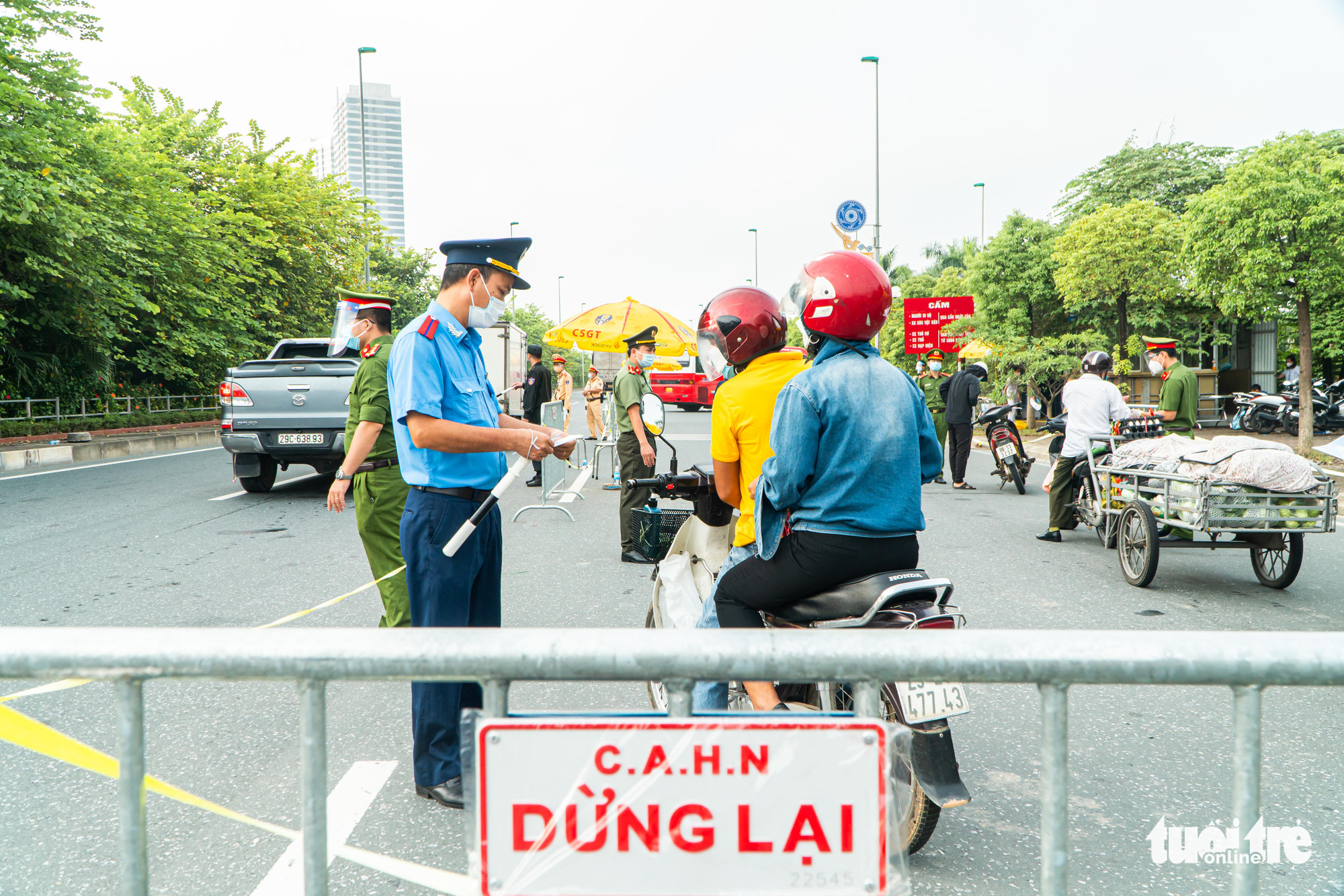 Officers examine commuters' travel passes at a checkpoint in Hanoi, September 6, 2021. Photo: Pham Tuan / Tuoi Tre