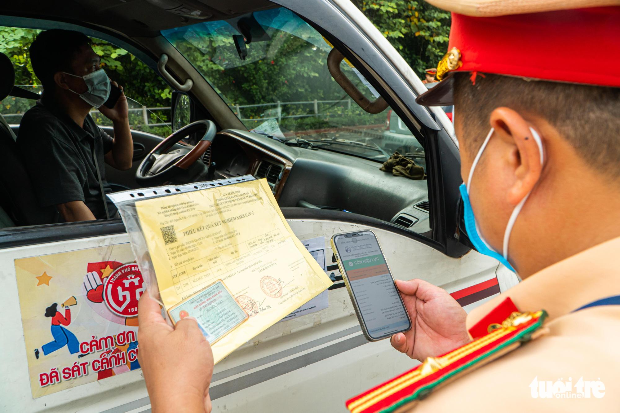 An officer checks documents of a car driver in Hanoi, September 6, 2021. Photo: Pham Tuan / Tuoi Tre