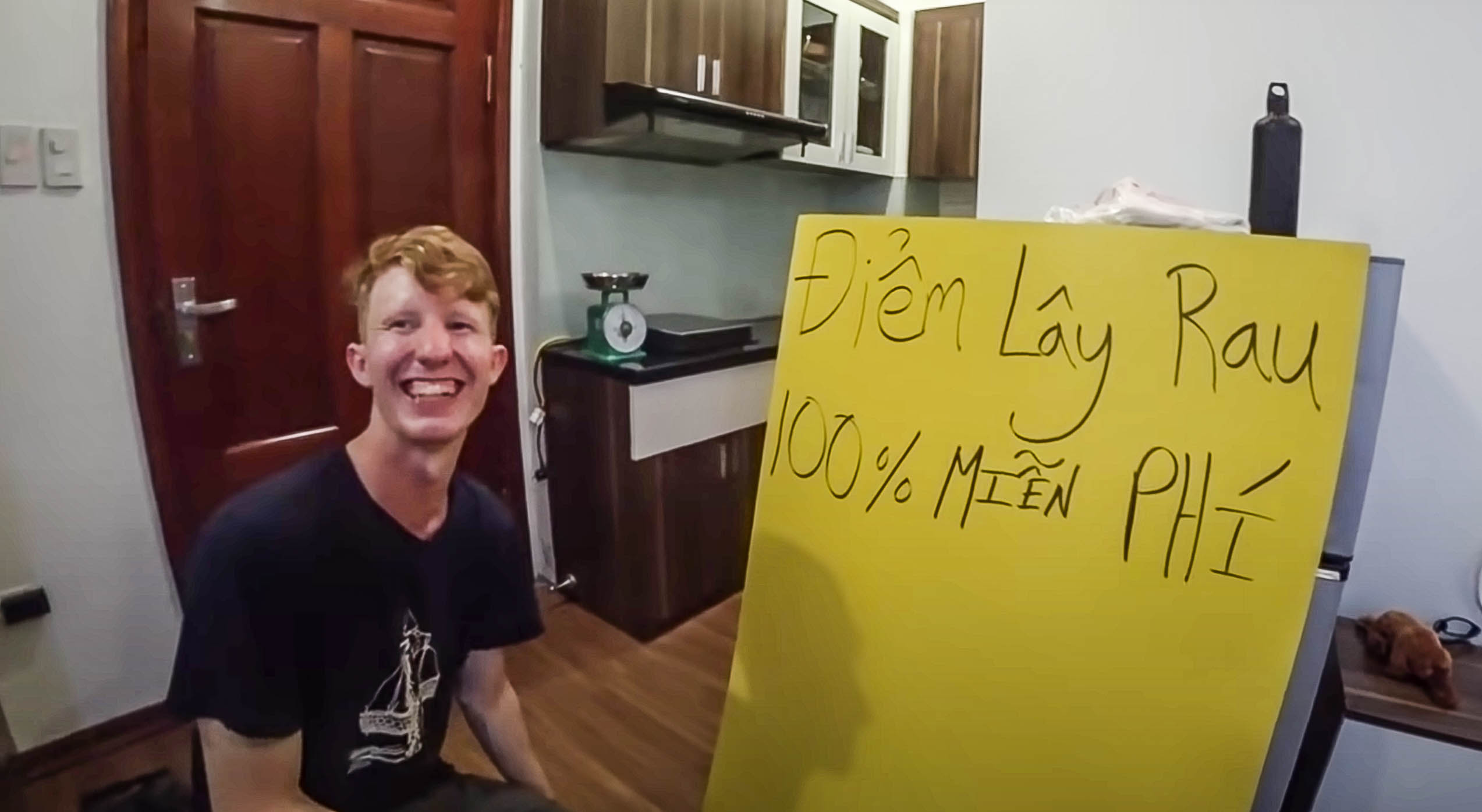Chris Lewis is seen in a snapshot from his YouTube video, with a board next to him saying '100 percent free vegetable pick up point.' Chris Lewis wrote the sign in Vietnamese himself.