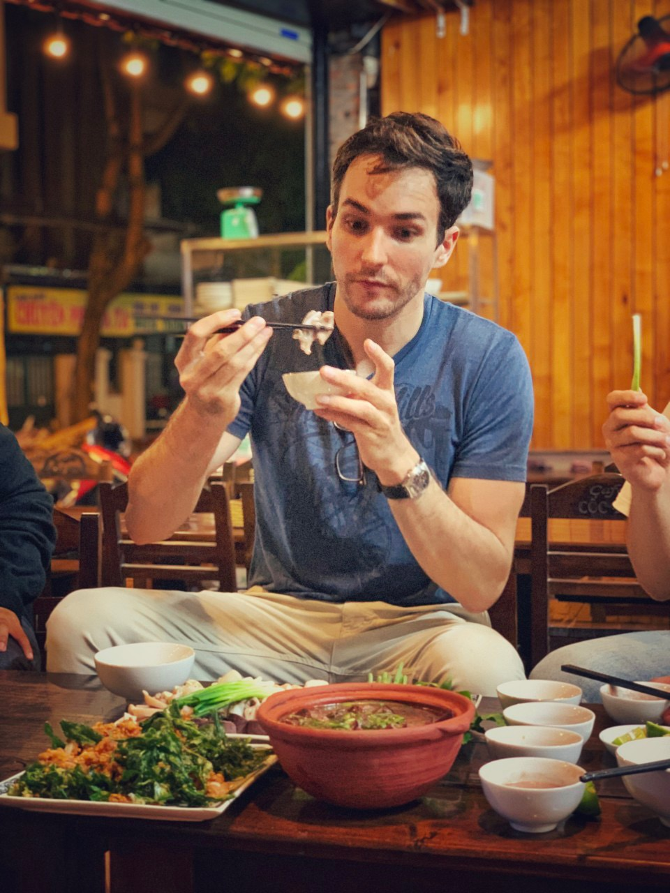 Will Courageux is trying pig intestines dipped in shrimp paste at a restaurant in Hanoi. Photo by courtesy of Will Courageux