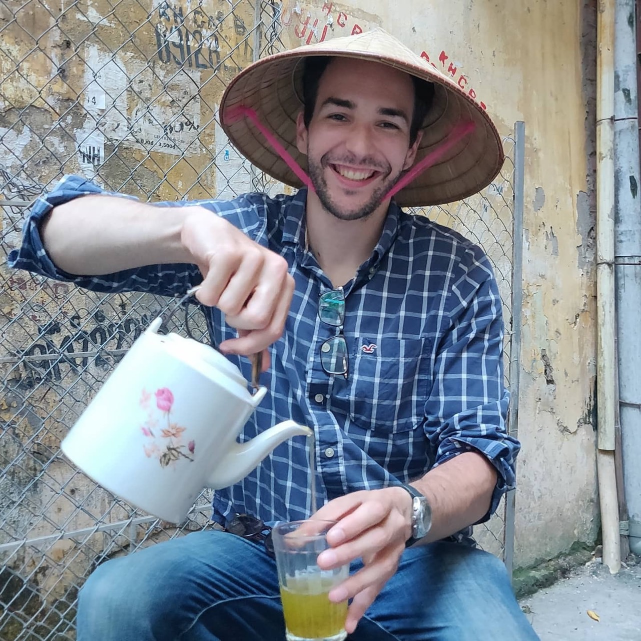 Will Courageux enjoys a glass of iced tea while wearing a Vietnamese conical hat in a picture taken in Hanoi.