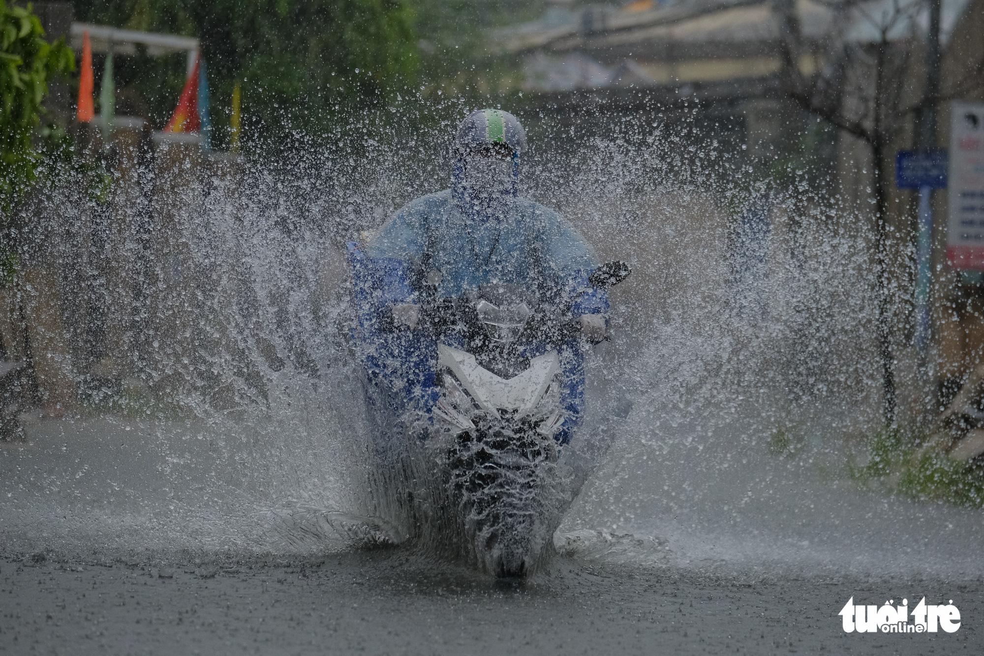 A motorcyclist travel on a flooded street in Da Nang City, Vietnam. Photo: Tan Luc / Tuoi Tre