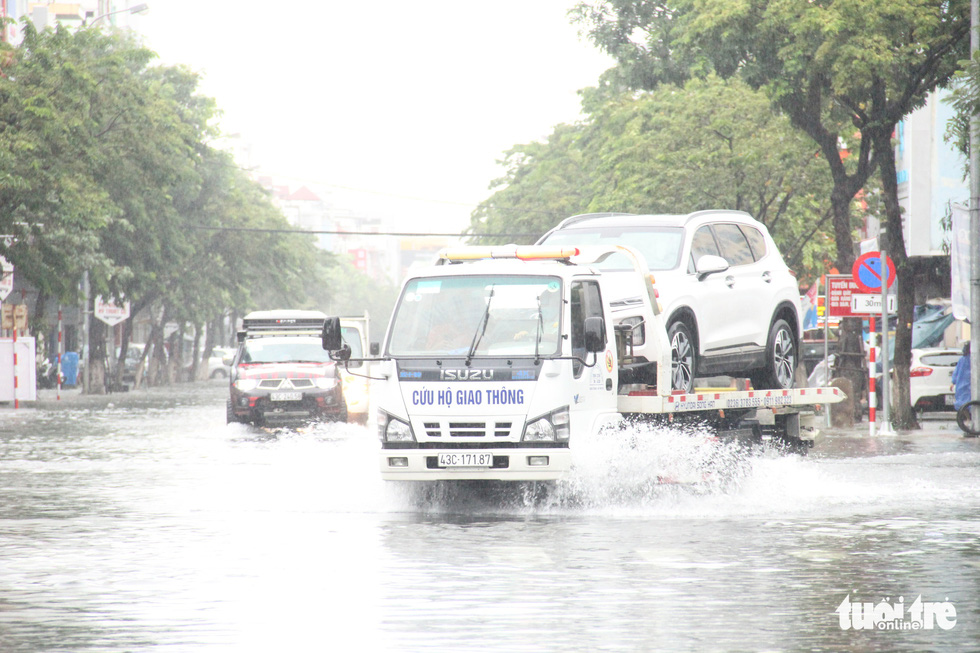 A rescue vehicle transports a car on a flooded street in Da Nang City, Vietnam, September 12, 2021. Photo: Truong Trung / Tuoi Tre