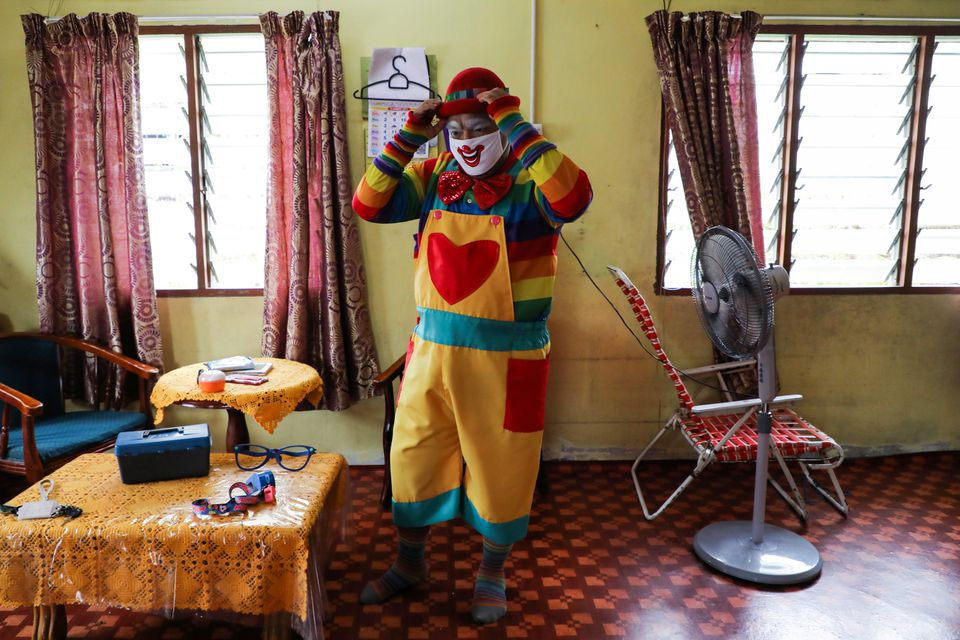 Shaharul Hisam bin Baharuddin, 43, puts on a clown outfit, as he prepares for disinfection, at his home in Taiping, Malaysia September 10, 2021. Photo: Reuters
