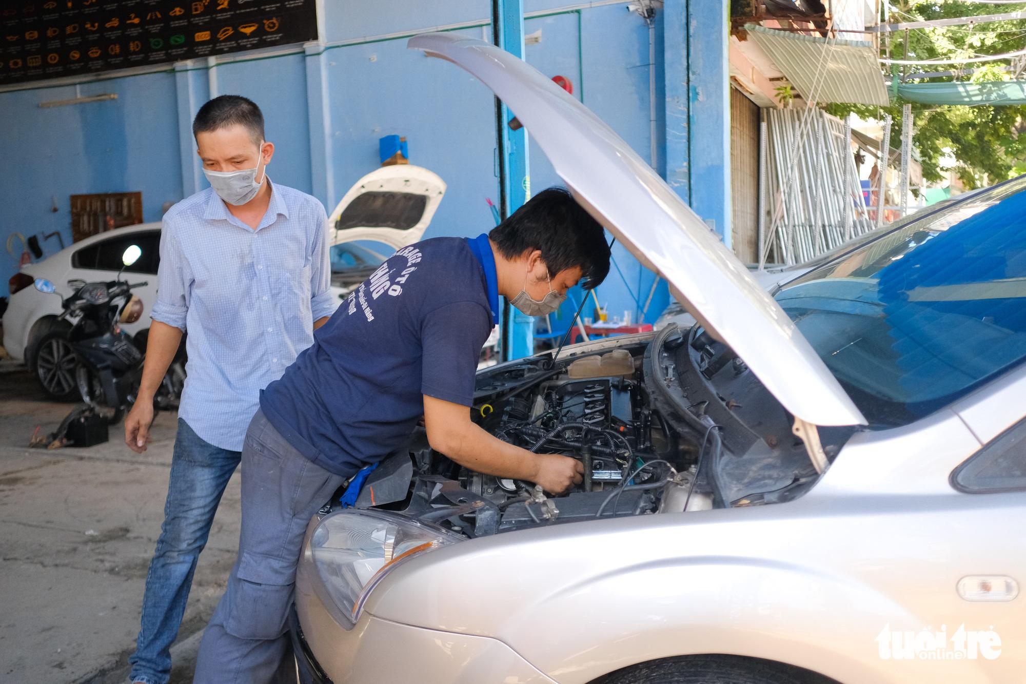 Workers repair a car at a garage in Lien Chieu District, Da Nang, September 16, 2021. Photo: Tan Luc / Tuoi Tre