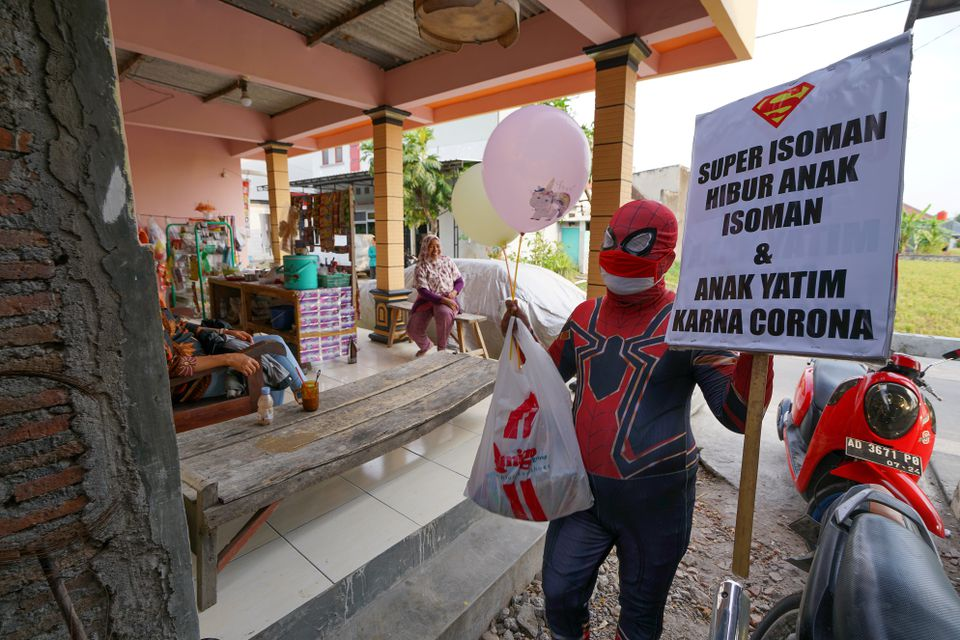 Agus Widanarko, 40, wearing a Spiderman costume, carries a sign that reads 'Super Isoman entertains isolated children and orphans due to the coronavirus disease (COVID-19)', as he prepares to bring cheer to children confined to their homes by COVID-19 restrictions, in Sukoharjo, Central Java province, Indonesia, September 10, 2021. Photo: Reuters