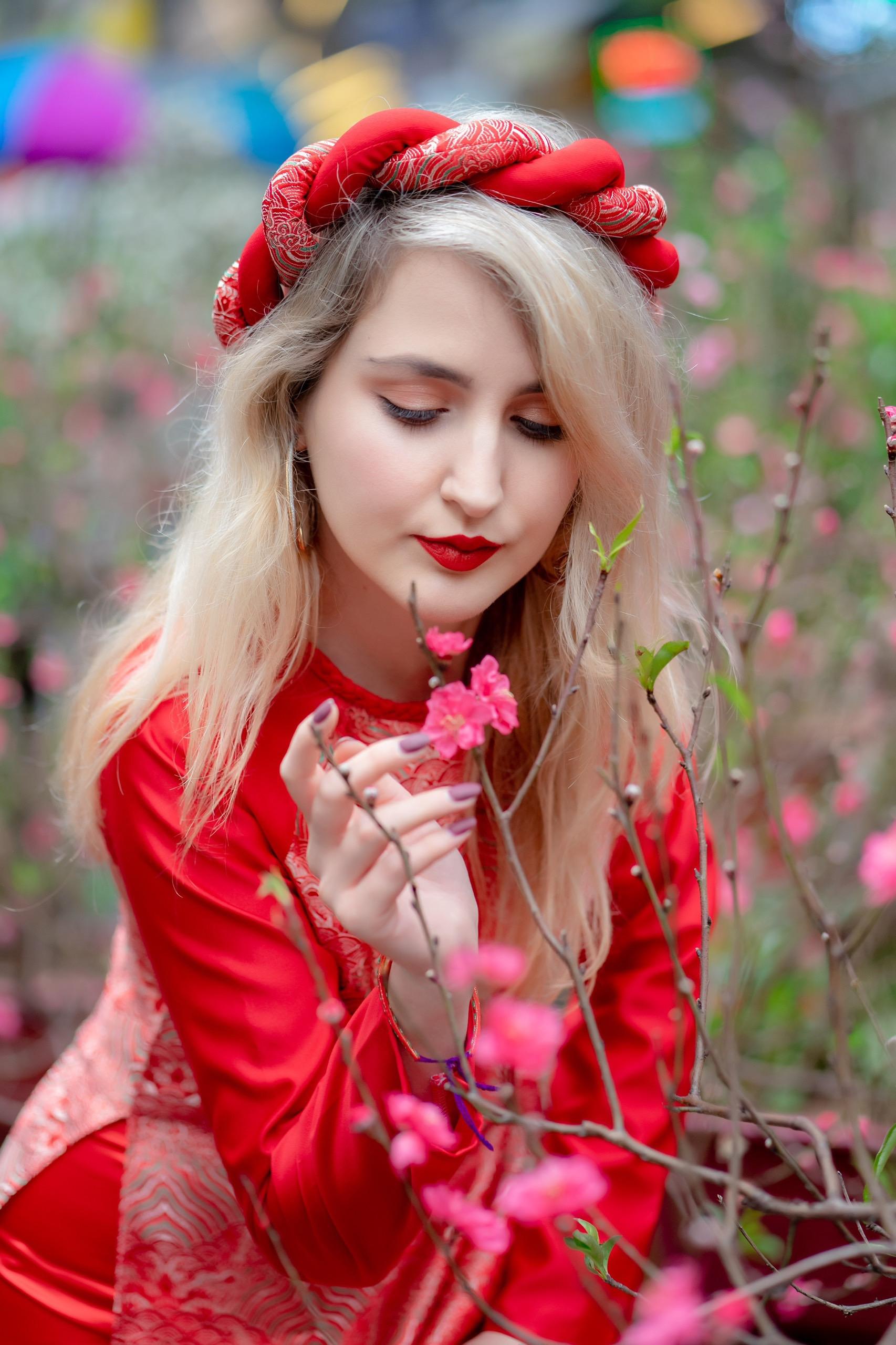 Dajana Hoxhaj wears ao dai (Vietnamese traditional costume) and poses with cherry blossoms, the flower symbolizing Tet (Vietnamese Lunar New year) in northern Vietnam. Photo by courtesy of Dajana Hoxhaj