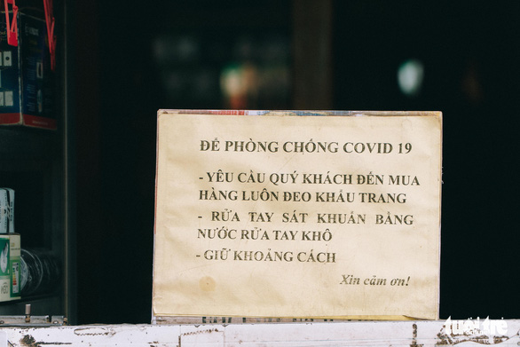 COVID-19 safety rules are written on a sign in front of a shop in Hanoi, September 16, 2021. Photo: Pham Tuan / Tuoi Tre