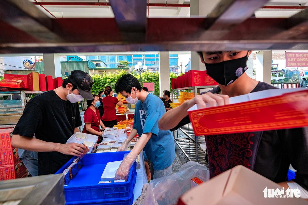 Bao Phuong staffers prepare mooncakes at a makeshift sale location on Thuy Khue Street, Tay Ho District, Hanoi, September 19, 2021. Photo: Nam Tran / Tuoi Tre