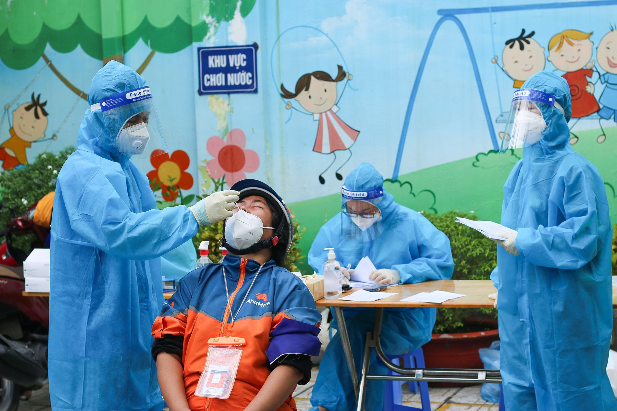 A medical worker takes a nasal swab from a delivery worker for COVID-19 testing on Nguyen Van Luong Street in Go Vap District, Ho Chi Minh City, September 20, 2021. Photo: Chau Tuan / Tuoi Tre