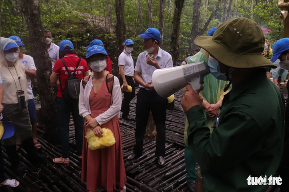 Visitors listen to a tour guide at Rung Sac Revolutionary Base in Can Gio District during a tour to pay tribute to medical workers from other localities that had come to assist Ho Chi Minh City in the fight against COVID-19 on September 19, 20201. Photo: Tuoi Tre