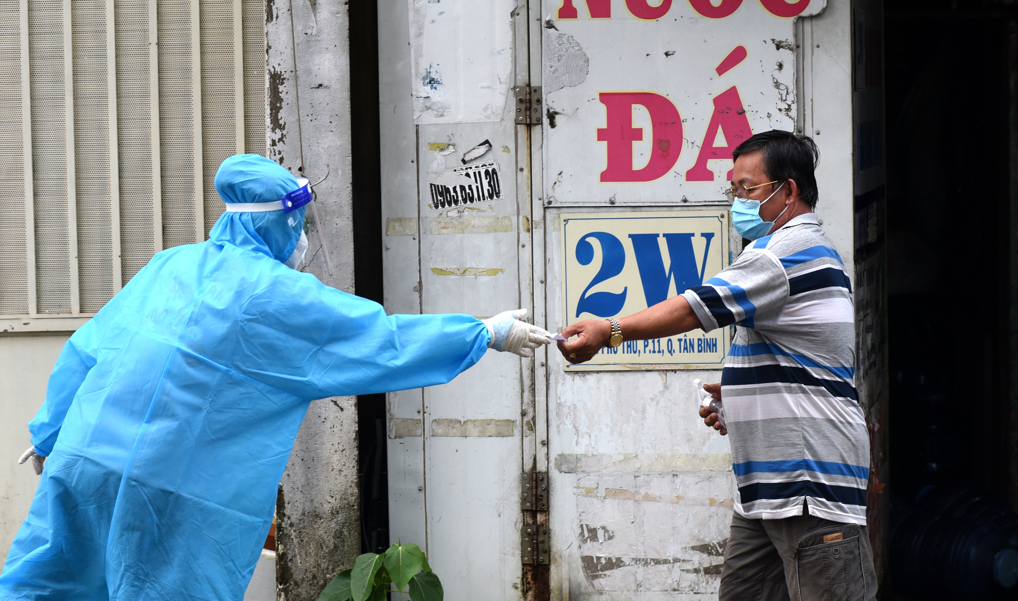 A medical worker gives a rapid antigen COVID-19 test kit to a resident of Tan Binh District in Ho Chi Minh City. Photo: Duyen Phan / Tuoi Tre