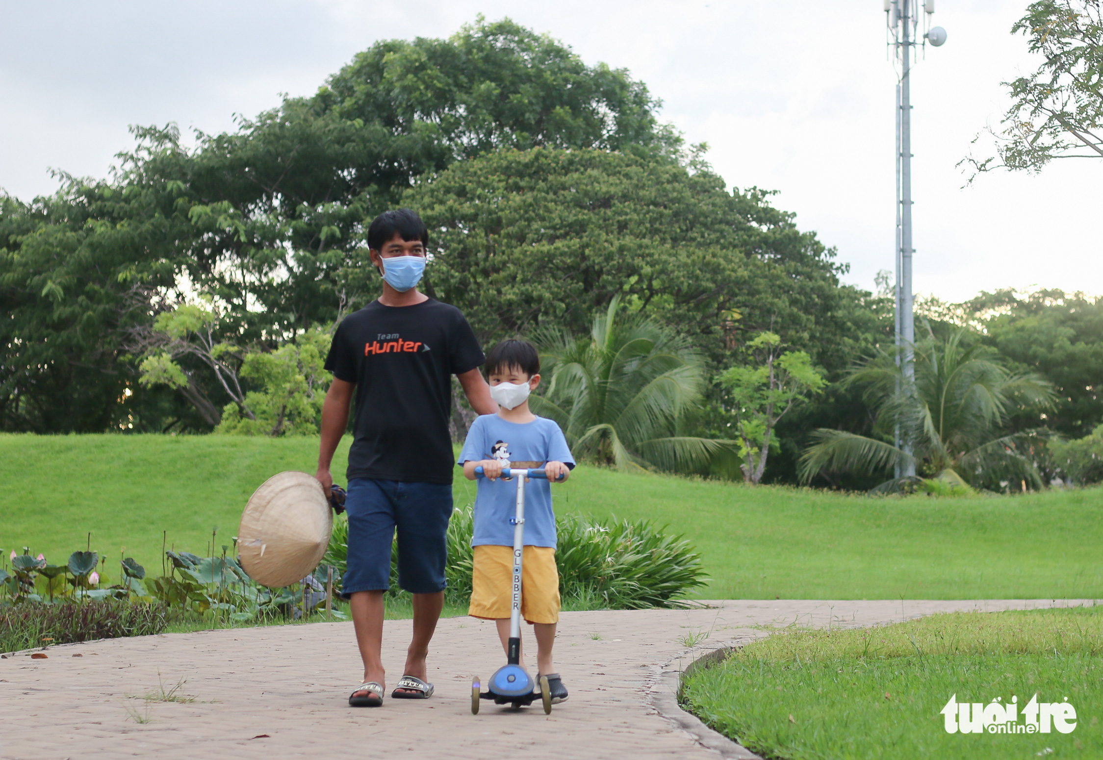 A man goes for a walk with his son at a park in District 7, Ho Chi Minh City, September 21, 2021. Photo: Chau Tuan / Tuoi Tre