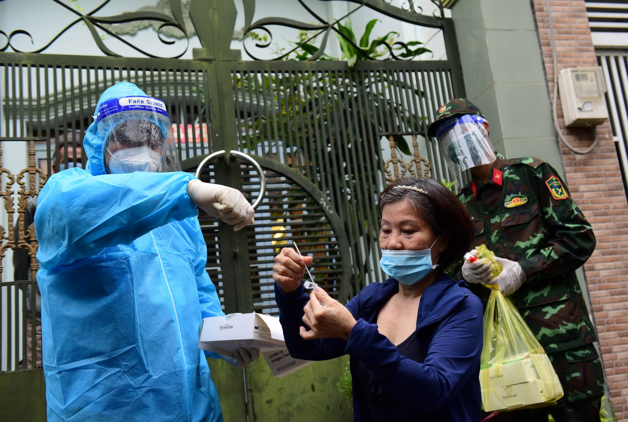 A medical worker instructs a resident take a COVID-19 test sample by herself in Go Vap District, Ho Chi Minh City, September 24, 2021. Photo: Duyen Phan / Tuoi Tre