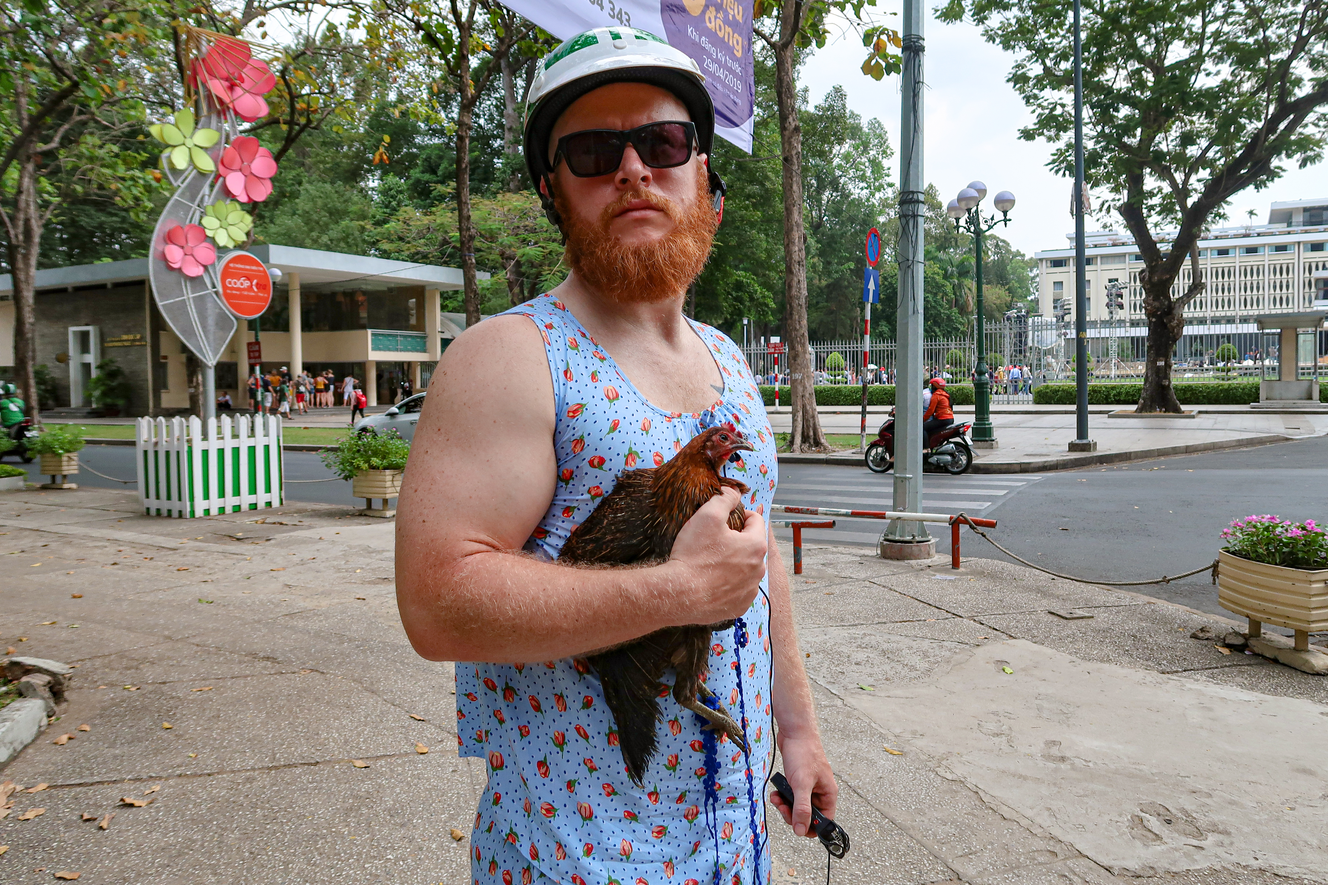 Brandon Hurley is seen wearing a Vietnamese women's pajamas in a photo taken with his pet chicken on the street of Ho Chi Minh City he provided Tuoi Tre News