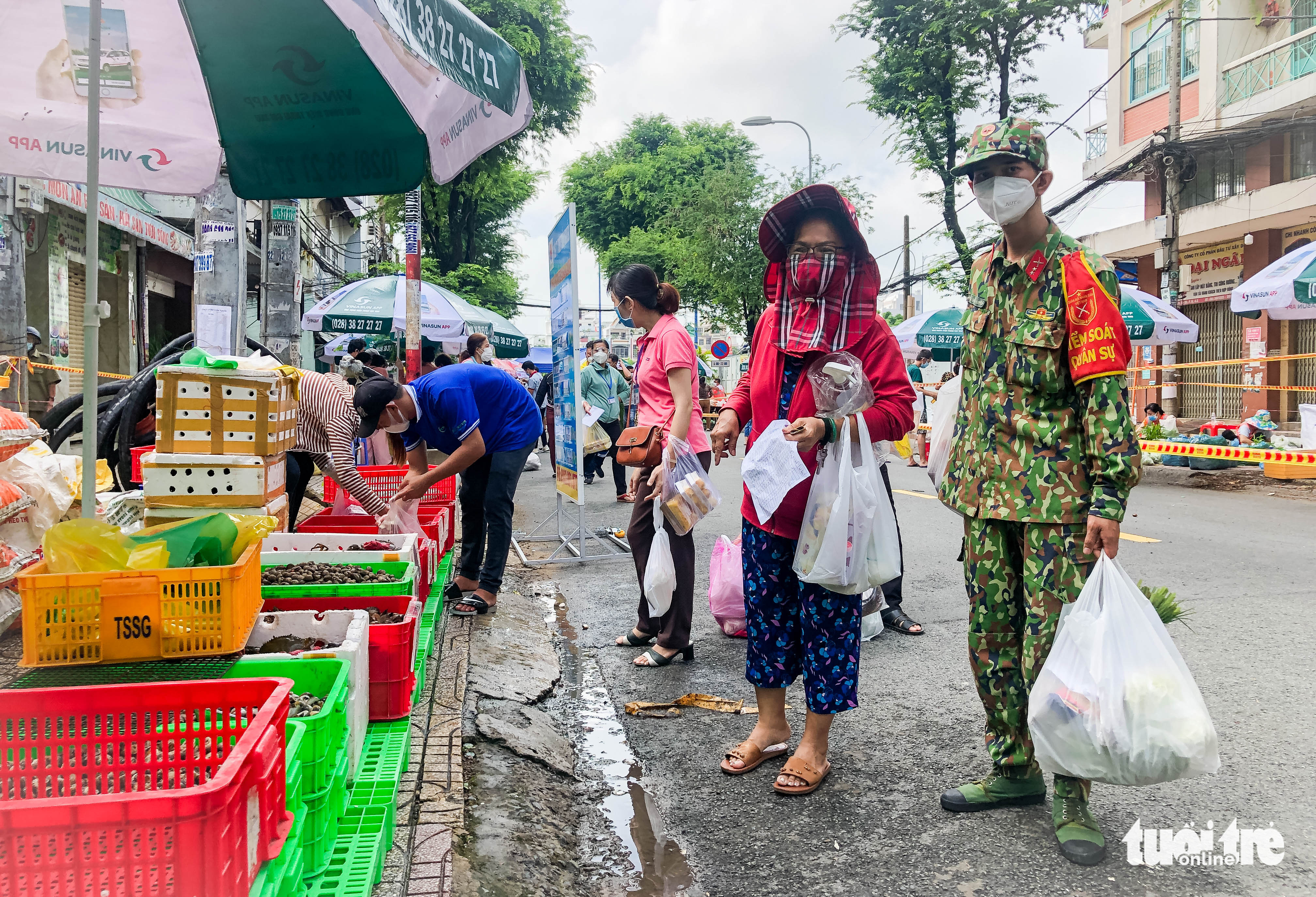 A military officer helps a resident carry groceries. Photo: Chau Tuan / Tuoi Tre