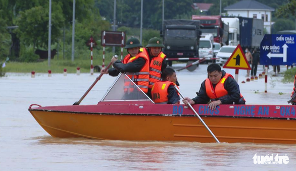 Officers use a boat to carry people through a flooded section on National Highway 48 in Nghe An Province, Vietnam. Photo: Hong Phong / Tuoi Tre