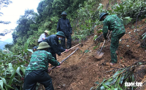 Border guard officers remove debris from a road hit by a landslide in Ky Son District, Nghe An Province, Vietnam. Photo: Le Thach / Tuoi Tre