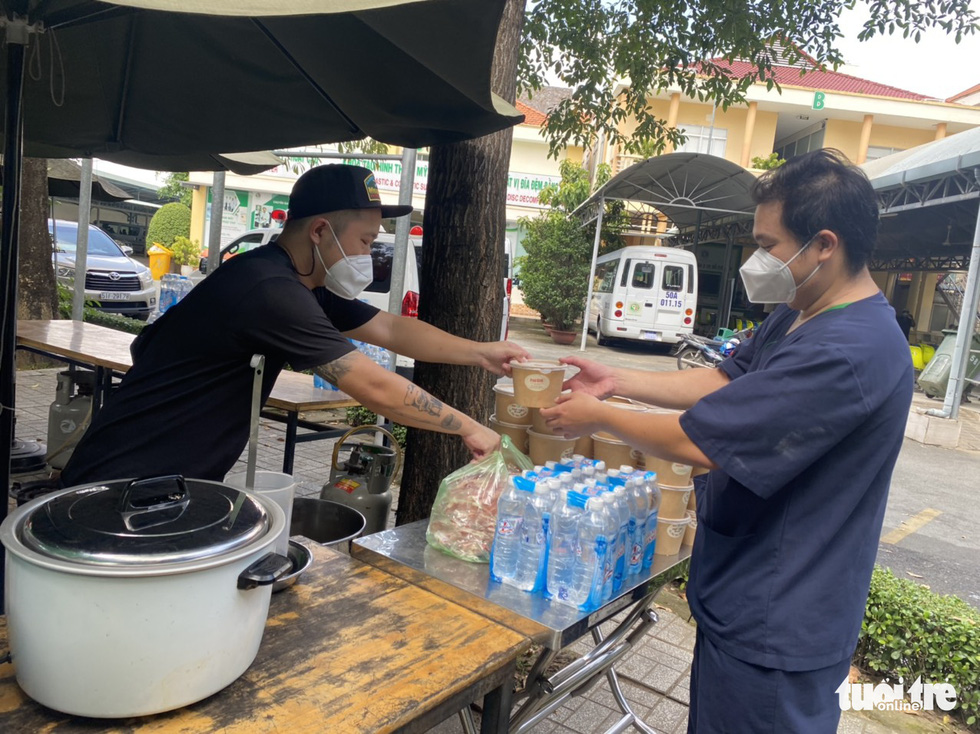 """Nguyen Xuan Chinh, owner of Pho Phu Gia, serves a bowl of pho to a medical worker at Le Van Thinh Hospital in Ho Chi Minh City's Thu Duc City as part of """"Xe Pho Yeu Thuong"""" (Loving Rides of Pho) sponsored by Tuoi Tre (Youth) newspaper on September 29, 2021. Photo: Tuoi Tre"""