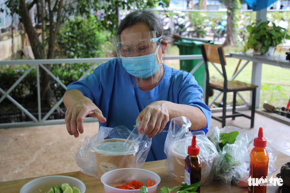 """Nen, a janitor at Le Van Thinh Hospital in Ho Chi Minh City's Thu Duc City, enjoys a bowl of pho served as part of an activity entitled """"Xe Pho Yeu Thuong"""" (Loving Rides of Pho) launched by Tuoi Tre (Youth) newspaper on September 29, 2021. Photo: Tuoi Tre"""