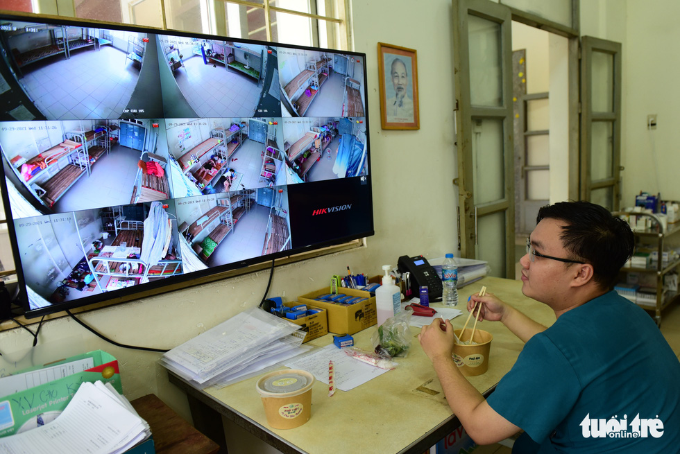 Doctor Cao Thanh Nguyen enjoys his pho while monitoring patients through a screen at a dormitory owned by the Ho Chi Minh City University of Technology and Education on September 29, 2021. Photo: Tuoi Tre