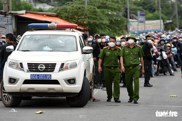 Functional forces prepare a police car to lead domestic migrant workers during their motorbike trip back to hometown in Vinh Cuu District, Dong Nai Province, Vietnam, October 2, 2021. Photo: A Loc / Tuoi Tre