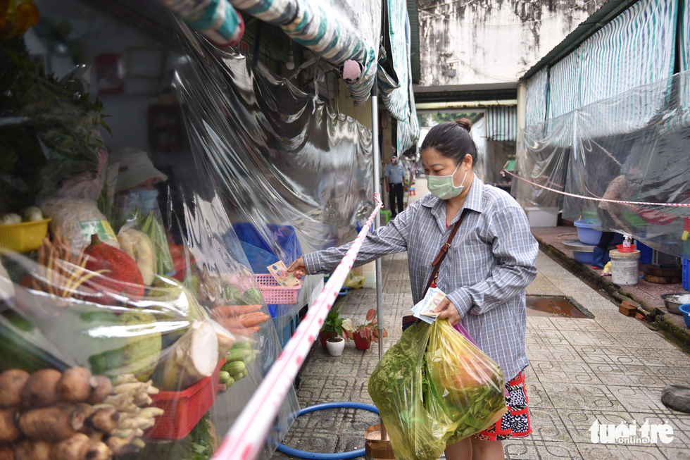 Nguyen Quynh Lam, a market goer, is seen putting money into a basket at the Ben Thanh Market. Photo: Ngoc Phuong / Tuoi Tre