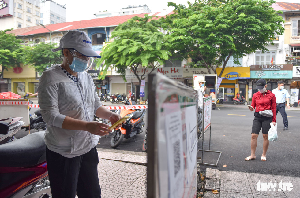 A resident has her QR code scanned for vaccination history check before entering the Ben Thanh Market in Ho Chi Minh City. Photo: Ngoc Phuong / Tuoi Tre